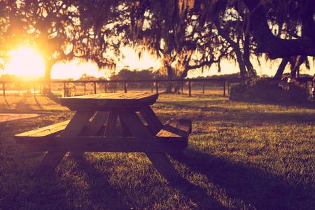 Hölzerner Picknicktisch in Feld mit Bäumen bei Sonnenuntergang Sonnenaufgang goldenen Stunde suchen friedliche ruhige meditative warmen restful