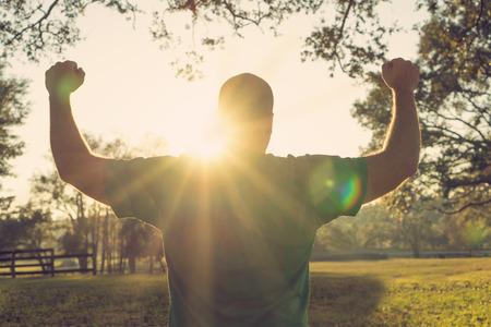 celebra: Hombre realizado feliz éxito de pie con los brazos en alto frente al sol. Atleta masculino blanco con los brazos hasta la celebración y feliz con su acheivement y ejercicio.
