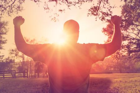 上げられた両手を太陽に直面して成功の幸せな達成の男が立っています。腕を祝って、彼の達成および運動と幸せと白のオスの運動選手。 写真素材