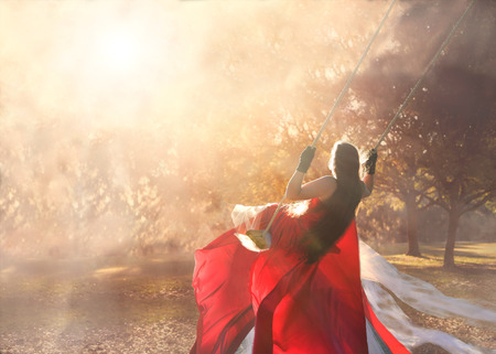 gown: Girl woman swinging outside in long formal gown dress with long brown hair looking off into the distance with sun beaming down on her in a magical mystical fantastical way