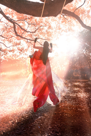 Girl woman swinging outside in long formal gown dress with long brown hair looking off into the distance with sun beaming down on her in a magical mystical fantastical way