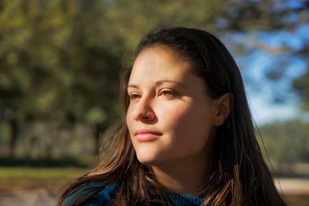 Portrait einer jungen weißen Frau mit braunen Haaren und hellen braunen Augen draußen im Sonnenlicht kontemplativen suchen nachdenklich wissen unlesbar unerreichbare