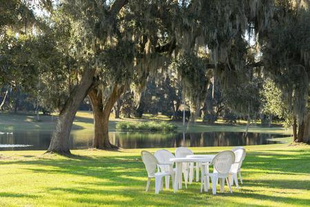 Weiße Plastiktisch und Stühle in einem Garten auf der grünen Wiese an einem Teich oder See in der Nachmittagssonne und eine ruhige entspannende ruhige ruhige Umgebung