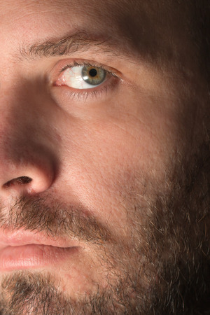 eyes hazel: Intimate closeup of a white  attractive man with mustache beard and hazel eyes looking intense serious thoughtful authentic real beautiful accusatory Stock Photo