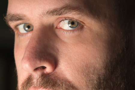 Intimate closeup of a white sexy hot attractive man with mustache beard and hazel eyes looking intense serious thoughtful authentic real beautiful accusatory Stock Photo