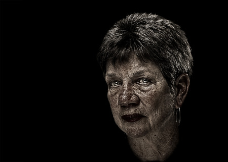 flaws: Portrait of a senior elderly older woman lady with short hair and desaturated with exaggerated flaws wisdom marks inlcuding wrinkles sunspots with serious judging melancholy sad depressed serious expression isolated on black background