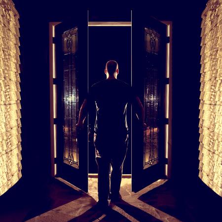 the welcome: Apertura hombre cerrando puertas de entrada dobles delanteros con vidrio en el vest�bulo por la noche desde atr�s mirando curioso miedo listo bienvenida abandono espeluznante entrar en el uknown Foto de archivo