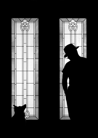 outcast: Silhouette of a man wearing a fashionable gangster mafia hat in a decorative window of a door looking mysterious solitary absorbed meditative reflective lonely thoughtful pensive patient dangerous serious as an outcast outsider secret Stock Photo