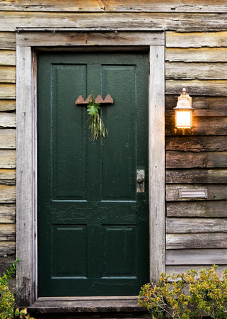 skewed: Old rustic vintage dilapidated antique house home building structure with green intricate front door and window with shutters closed and porch light lantern glowing turned on