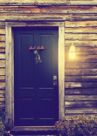 skewed: Old rustic vintage antique house home building structure with green intricate front door and window with shutters closed and porch light on Stock Photo