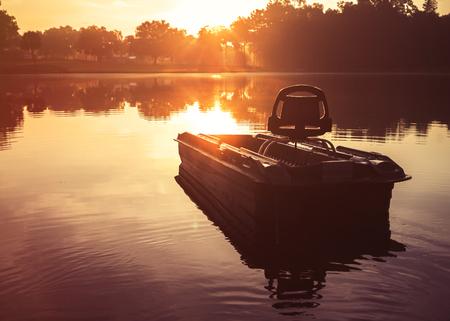 Kleine leere Fischerboot auf See Flusswasser Teich bei Sonnenaufgang Sonnenuntergang Dämmerung am frühen Morgen der Dämmerung mit Sonnenstrahlen und Bäume Wald am Horizont Gefühl friedlich entspannt heiter meditative Ruhe Lizenzfreie Bilder