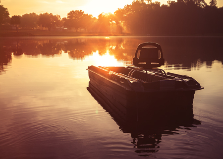 fishing lake: Small empty fishing boat on lake river water pond at sunrise sunset dawn early morning dusk with sun rays and trees forest on horizon feeling peaceful relaxed serene calm meditative Stock Photo
