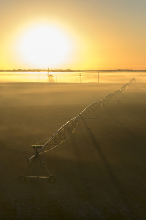 pivot: Rural farm countryside pivot irrigation system on an empty barren field at sunrise or sunset in the fog or mist Stock Photo