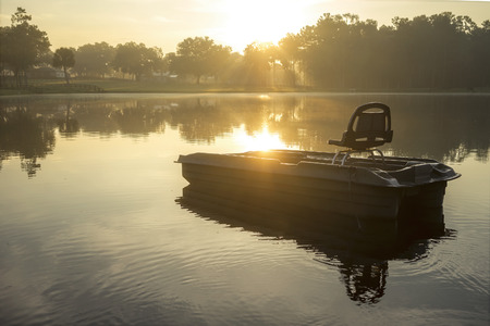 meditative: Small empty fishing boat on lake river water pond at sunrise sunset dawn early morning dusk with sun rays and trees forest on horizon feeling peaceful relaxed serene calm meditative Stock Photo