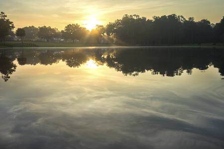 sunset lake: Empty lake river water pond at sunrise sunset dawn early morning dusk with sun rays and trees forest on horizon and coulds reflected feeling peaceful relaxed serene calm meditative