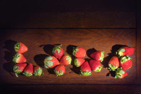 imperfect: Natural imperfect strawberries on wooden table spelling out the word love with a vintage rustic filter and dramatic passionate lighting