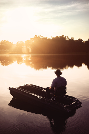 Man in hat sitting in small fishing boat on lake river water pond at sunrise sunset dawn early with sun rays and trees forest on horizon feeling peaceful relaxed serene calm meditative lonely alone