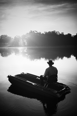 bateau de pêche: Man in hat sitting in small fishing boat on lake river water pond at sunrise sunset dawn early with sun rays and trees forest on horizon feeling peaceful relaxed serene calm meditative lonely alone