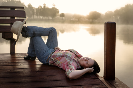 dark brown hair: Girl woman lady female caucasian with long dark brown hair lying down on a lake pond dock with reflections at sunrise or sunset in cowboy hat flannel shirt looking relaxed happy serene beautiful young  peaceful