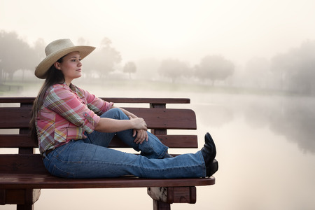 Girl woman lady female caucasian with long dark brown hair sitting on wood bench by foggy lake pond dock in cowboy hat flannel shirt looking relaxed happy serene beautiful young peaceful