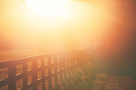 transcendence: Rural country farm ranch three board wood fence under sunset or sunrise sunbeams with lens flare looking romantic divine heavenly mysterious warm serene transcendent