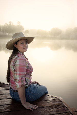 dark brown hair: Girl woman lady female caucasian with long dark brown hair sitting on a foggy lake pond dock with reflections at sunrise or sunset in cowboy hat flannel shirt looking relaxed happy serene beautiful young peaceful Stock Photo