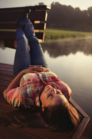Girl woman lady female caucasian with long dark brown hair lying down on a lake pond dock with reflections at sunrise or sunset in cowboy hat flannel shirt looking relaxed happy serene beautiful young  peaceful