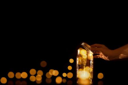 coger: recipiente transparente de vidrio jarro claro con las bolas mágicas de puntos trozos de luz bokeh dejando escapar o ser liberado dejado libres desde la captura de confinamiento aislado en el fondo negro