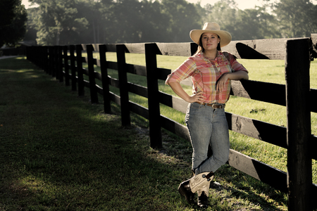 Cowgirl lady woman female wearing cowboy hat and flannel shirt with jeans leaning on country rural fence by a horse pasture paddock looking confident happy serene smart alone waiting watching patient