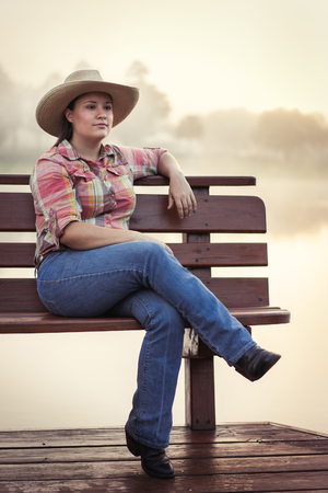 long lake: Girl woman lady female caucasian with long dark brown hair sitting on wood bench on foggy lake pond dock in cowboy hat flannel shirt looking relaxed happy serene beautiful young peaceful Stock Photo