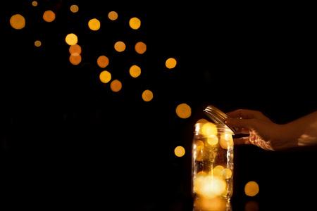 Klar transparent krug Glasbehälter mit magischen Kugeln Pünktchen Bits Bokeh Licht verlassen zu entkommen oder let aus der Gefangenschaft capture isoliert auf schwarzem Hintergrund gehen frei freigegeben werden