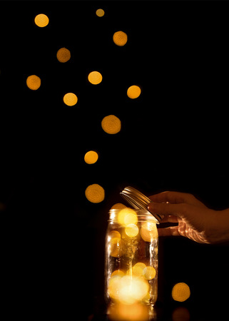 emanate: Clear transparent jar jug glass container with magical balls dots bits of bokeh light leaving escaping or being released let go free from confinement capture isolated on black background Stock Photo
