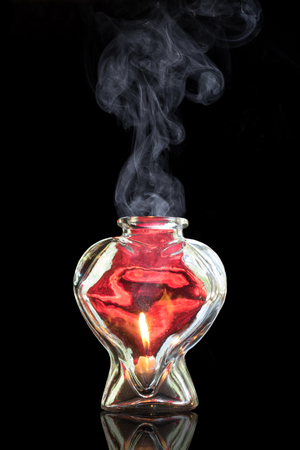 spell: Smoke rising from red glass heart with fire flame inside representing romance potion love hope memory hardship connection anniversary dating valentines infatuation elixir danger emotion essence Stock Photo