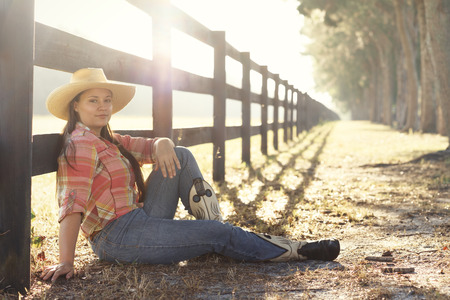 Cowgirl lady woman female wearing cowboy hat and flannel shirt with jeans sitting leaning on country rural fence by a horse pasture paddock looking confident happy serene smart alone waiting watching patient