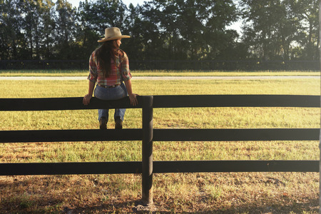 Cowgirl lady woman female wearing cowboy hat and flannel shirt with jeans sitting on country rural fence by a horse pasture paddock looking confident happy serene smart alone waiting watching patient