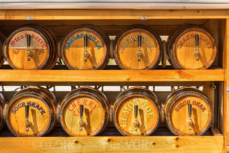 quench: Handcrafted homemade old fashioned soda pop barrel or keg dispensers with spouts ready to quench thirst with refreshment beverages Stock Photo