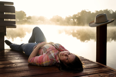 flannel: Girl woman lady female caucasian with long dark brown hair lying down on a lake pond dock with reflections at sunrise or sunset in cowboy hat flannel shirt looking relaxed happy serene beautiful young  peaceful