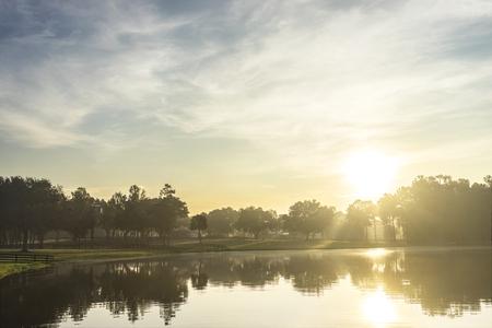 Petit lac vide étang d'eau de la rivière au lever du soleil l'aube au crépuscule du matin avec les rayons du soleil et des arbres forêt horizon sentiment paisible détendue sereine calme méditatif Banque d'images