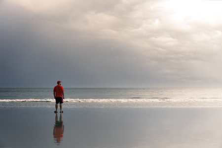 Man standing on beach while storm comes in looking toward the sun Imagens