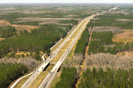 Aerial view of rural tree covered countryside with highway Imagens