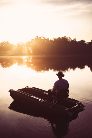 Man in small fishing boat on lake river water pond at sunrise sunset dawn early morning dusk with sun rays and trees forest on horizon feeling peaceful relaxed serene calm meditative alone sad lonely on vacation Imagens