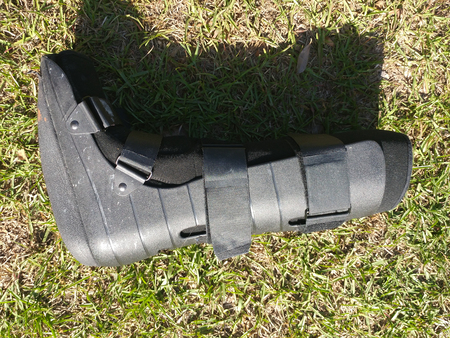A black Orthopedic or medical boot, cast or footwear, laying on side, view from the back, isolated on bright green summer grass.