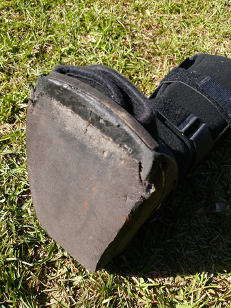A black Orthopedic or medical boot, cast or footwear, isolated on bright green summer grass, white paint splatter on lower strap, closeup of the bottom as worn, tattered, and frayed. Stock Photo