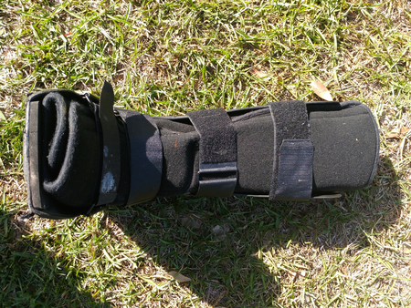 A black Orthopedic or medical boot, cast or footwear, isolated on bright green summer grass, laying down face up. Stock Photo