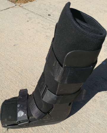 A black Orthopedic or medical boot, cast or footwear, profile view with toes to the left, isolated on concrete with a white paint splatter on the lower buckle.