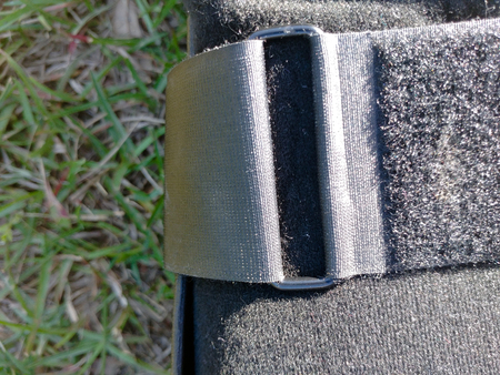 A black Orthopedic or medical boot, cast or footwear, isolated on bright green summer grass, closeup of metal buckle and velcro strap.