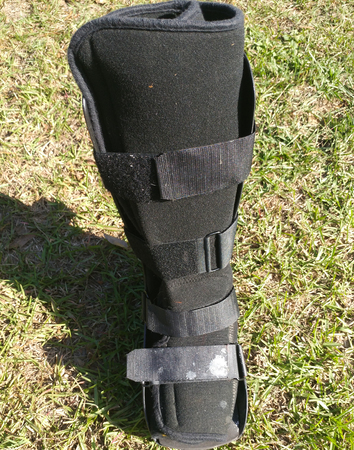 A black Orthopedic or medical boot, cast or footwear, view of the front, isolated on bright green summer grass, white paint splatter on lower buckle. Banco de Imagens