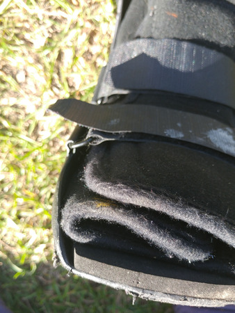 A black Orthopedic or medical boot, cast or footwear, isolated on bright green summer grass, white paint splatter on lower strap, closeup of toes.