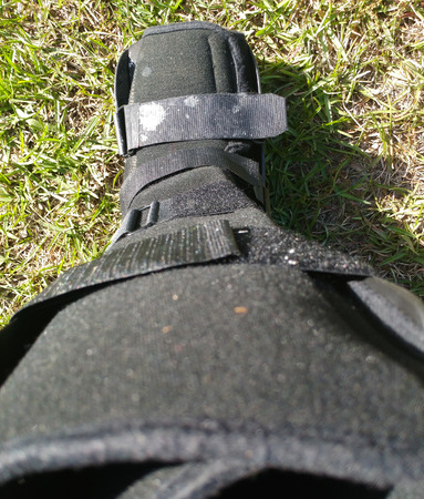 A black Orthopedic or medical boot, cast or footwear, perspective looking down towards the toes of the boot, isolated on green summer grass, white paint splatter on lower buckle.