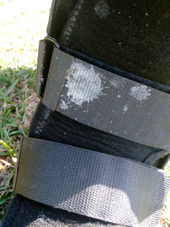 A black Orthopedic or medical boot, cast or footwear, isolated on bright green summer grass, closeup view of  white paint splatter on lower strap.